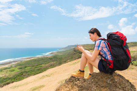 女性は家族や友人の丘上から見る海岸の景色の上に座って運ぶバックパックをハイキングするときに連絡先をチャットと携帯電話を使用して。 写真素材