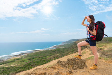 young beautiful female backpacker standing on hill mountain top looking at coastal scenery and enjoying sea breeze in leisure afternoon.