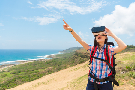 asian chinese female tourist holding the VR technology equipment and pointing to the blank copyspace experience 3D video when she hiking climbed to the top of the hill with blue ocean background.