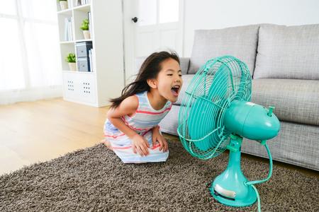 電動ファンを笑いと自宅のリビング ルームで夏休みを楽しんでいるクールな風を再生する素敵な若い女性の子供に直面します。