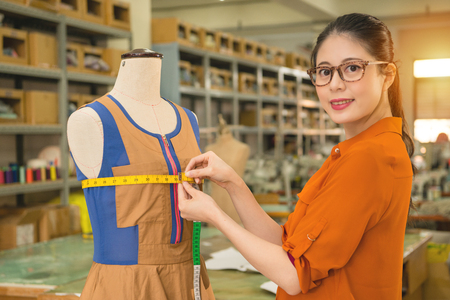 smiling professional beautiful costume tailor using tape measure dummy clothing dress bust and face to camera confident in factory tailor studio. Фото со стока