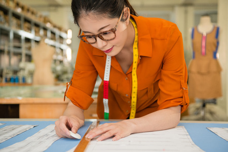 closeup photo of woman designer in pattern office studio drawing new clothing products for new season measured by chalk and ruler with profession and job occupation concept. Stock Photo