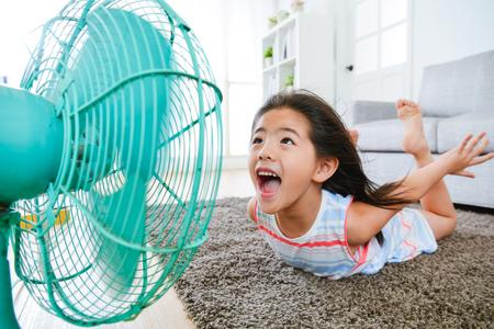 生活上に横たわって甘い美しい小さな子供部屋の床とセレクティブ フォーカス写真でポーズを飛んでクールな風を楽しむ扇風機に直面します。