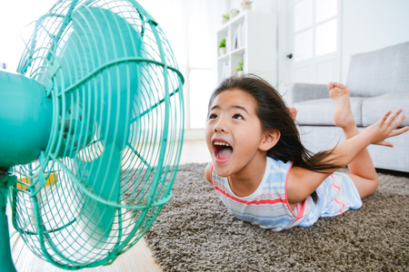 sweet beautiful little children lying down on living room floor and face to electric fan enjoying cool wind with flying posing with selective focus photo. Stock fotó - 83257947