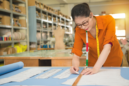 young beauty happy fashion tailor using chalk and long ruler on draft paper painting mark design new clothes in manufacturing office studio for pattern. profession and job occupation concept. Stock Photo