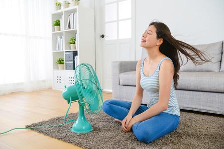 뷰티 젊은 여자 거실에 앉아 하 고 집에서 여름 시즌 열을 제거하는 것에 대 한 시원한 바람 즐기고 전기 팬을 사용합니다. 스톡 콘텐츠