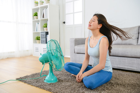 beauty young woman sitting on living room and using electric fan enjoying cool wind for eliminating summer season heat at home. Standard-Bild