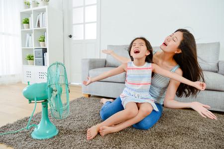 glückliches kleines Mädchen, das auf jungen Mutterbeinen sitzt und bequemen kühlen Wind des elektrischen Fans zusammen an der Sommersaison im Wohnzimmer genießt.