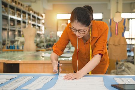 プロの若い女性のテーラー カッター デザイン パターンに沿ってハサミ工場システム スタジオの服のサンプルを作るための生地をカットを保持して 写真素材