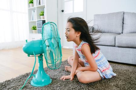 Reizendes blondes Mädchen der Jugendlichen , das auf Wohnzimmerboden spielt elektrische Stange spielt und genießt natürliches Wetter an der Sommerzeit zu Hause Standard-Bild