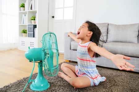 かなり満足の女性子供は、扇風機からのしい風を楽しんで、夏休みで居間の床の上に座って腕を開きます。 写真素材