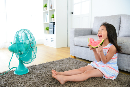 happy little girl children sitting on living room floor blowing electric fan cool wind and eating fresh watermelon feeling comfortable at summer. Фото со стока