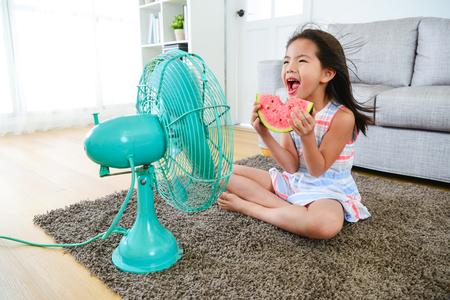 Chica hermosa de la juventud que sostiene la sandía que se sienta delante del ventilador eléctrico y sopla el ventilador fresco para eliminar el calor del verano Foto de archivo - 83258128