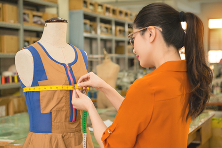 design department student learning how to design clothing using tape to measure dummy clothes for understand the design size in  factory manufacturing office. Stock Photo