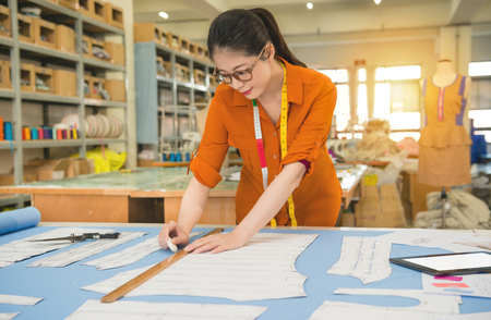 beautiful woman designer profession and job occupation concept. lady drawing sketch for new clothing pattern design in fashion studio with chalk and ruler. Stock Photo