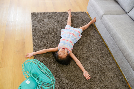 high angle photo of happy cute little girl lying down on floor and enjoying electric fan blowing cool wind in summer day.