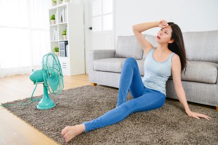 美しい甘い女性感じ暑いと頭痛扇風機しい風を楽しむリビング ルームの床の上に座って痛みを伴う。