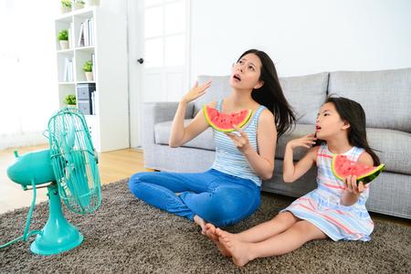여름 날 매우 뜨거운 느낌이 귀여운 작은 딸과 함께 예쁜 어머니와 전기 팬 시원한 바람 부는 수 박 먹고. 스톡 콘텐츠