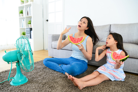 pretty mother with cute little daughter feeling very hot at summer day and eating watermelon blowing electric fan cool wind. Stockfoto