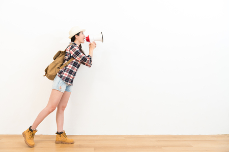 loudspeaker: young pretty woman standing on wooden floor looking at white wall background and using megaphone speaking showing travel concept.