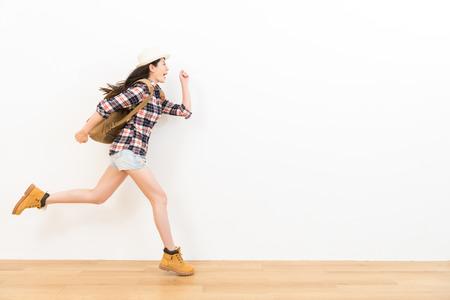 gelukkige Aziatische reiziger op de houten vloer die prestaties van de houding toont van het opgewekte lopen naar lege copyspace met witte muurachtergrond voor reis reclame.