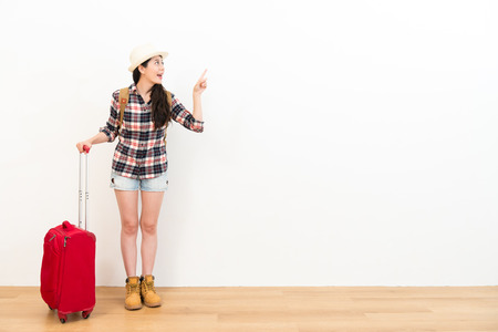 happy smiling woman backpacker holding travel suitcase and pointing white background empty area standing on wooden floor.