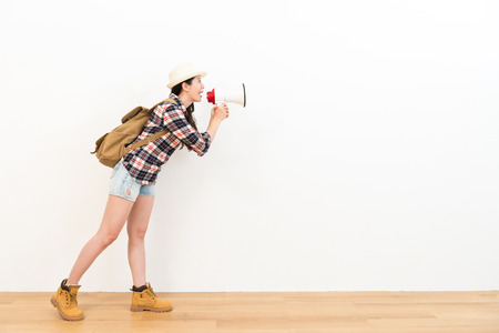 loudspeaker: happy female backpacker holding loudspeaker talking wearing travel clothing standing on wooden floor and announce travel information to white wall background . Stock Photo