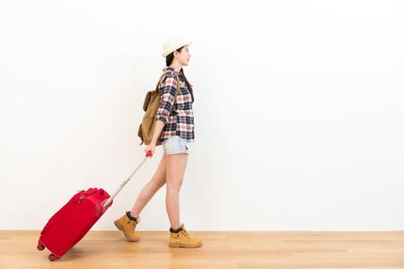 幸せな甘いバックパッカーの女性が旅行に行くと、背景が白い壁に木の床の上を歩く個人のスーツケースを運ぶ計画。