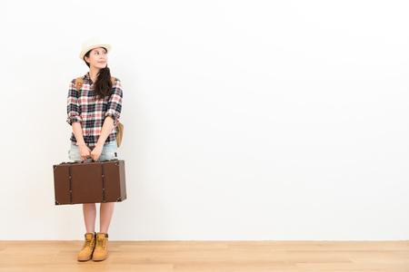 美しい笑みを浮かべて旅人女性持株ヴィンテージ スーツケースの上に立って木の床と白い壁の背景を見て旅行を待ちます。