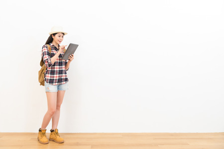 smiling female backpacker using digital tablet computer searching tourist destination guidebook through internet standing on wooden floor with white wall background.