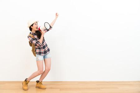gelukkige vrolijke vrouw kijken naar witte achtergrond maken overwinning winnaar vieren gebaar en het gebruiken van luidspreker aangekondigde informatie over houten vloer. Stockfoto