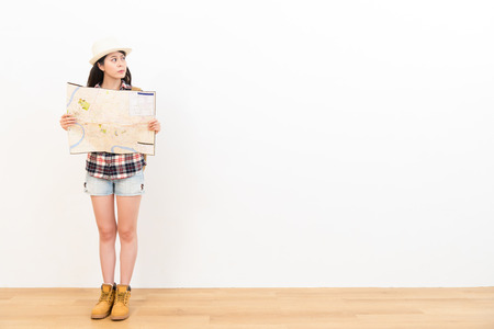 young beautiful female student holding paper map chagrin looking at copyspace worry about travel planning standing on wooden floor with white wall background.