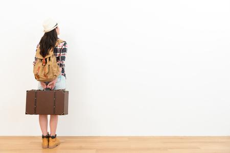다시보기 사진 꽤 젊은 여행자 여자 나무 바닥에 서서 흰 배경에 여행 계획에 대해 생각하고 복고풍 가방을 들고. 스톡 콘텐츠