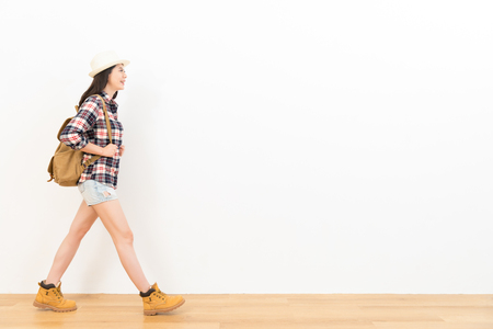 pretty female student wearing casual clothes as the backpacker going to copyspace area travel visit walking on the wooden floor with white wall background. Stock Photo