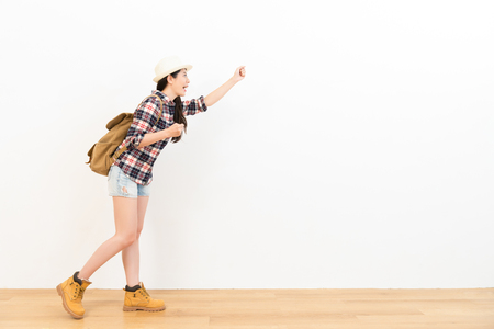 relaxed chinese mixed race backpacker on the wooden floor which performed ready to start travel posing and gestures happily looking at the blank copyspace with white wall background.