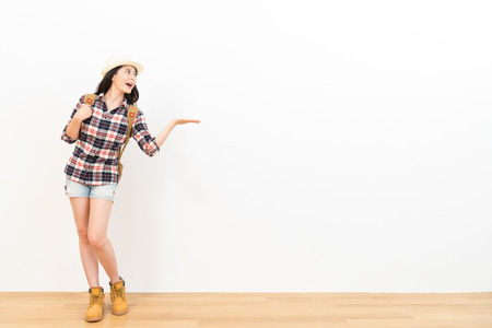 happy chinese backpacker making gestures of presentation showing text on the white wall background wearing travel clothing standing on the wooden floor looking at the blank copyspace. Фото со стока