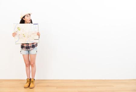 충격 된 여성 여행자 흥분 copyspace 영역에서 찾고 깜짝 여행 정보 나무 바닥과 흰색 배경에지도 들고. 스톡 콘텐츠