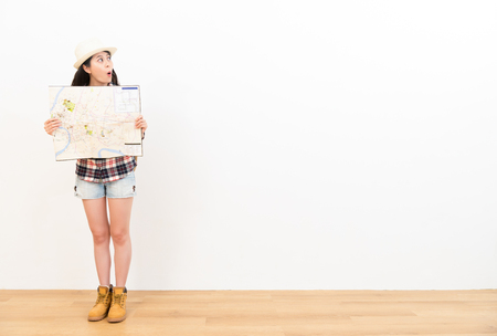 shocked female traveler excitedly looking at copyspace area feeling surprise travel information holding map on white background with wood floor. Stockfoto