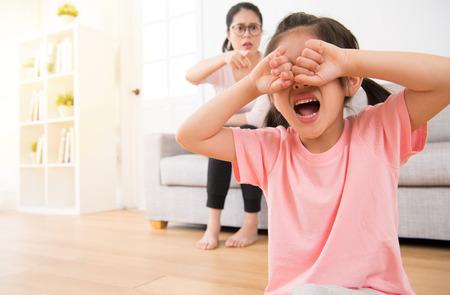 슬픈 작은 아이 소녀 나무 바닥에 앉아 큰 소리로 우는 거실에서 소파에 앉아 그녀를 가리키는 어머니 휴일의 아침에 화가 저주.