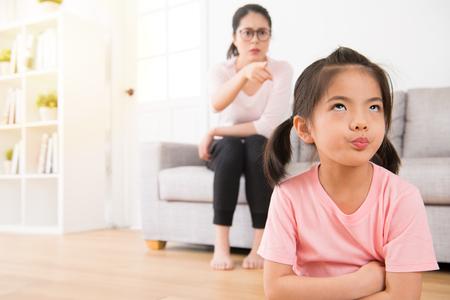 Los niños adorables jóvenes se aburreban con su madre enojada que regaña ruidosamente que siente el odio impaciente que molesta cuando mamá estaba sentada detrás de ella en el sofá en la sala de estar en casa. Foto de archivo - 89343767