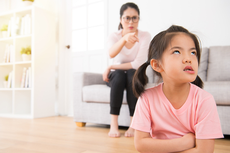 asian mother sitting on the back of the sofa angry pointing to the impatient and unhappy expression of the little girl seriously at home while children making mistake.