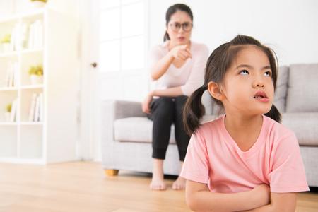 Die asiatische Mutter, die auf der Rückseite des Sofas sitzt, verärgerte das Zeigen auf den ungeduldigen und unglücklichen Ausdruck des kleinen Mädchens ernsthaft zu Hause, während Kinder Fehler machten.
