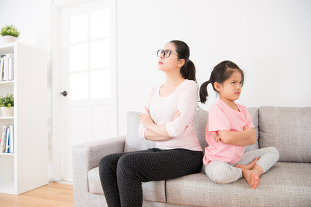 the young mother and the little daughter back to the back sitting on the sofa in the living room and each other to ignore each other after the quarrel feeling very angry. Stock Photo