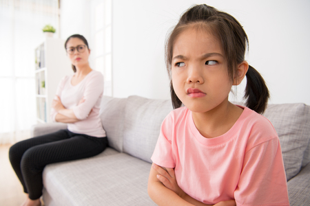 asian cute little girl expression face is not happy, hated looking at the rear blurred female guest at home sitting on a comfortable sofa with  beautiful woman.