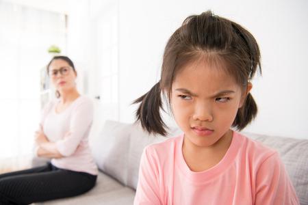 hermosa hija pequeña que comete errores, su madre la regaña en voz alta, la hace sentirse triste y muy enojada en su casa, en la sala de estar sentada en el sofá.
