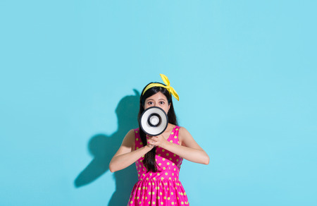 lovely beauty girl wearing cute dress standing on blue background and face to camera using loudspeaker announce information.