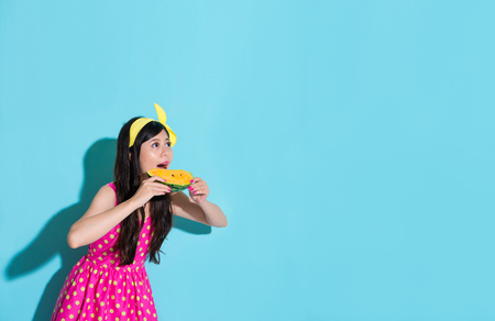 attractive pretty girl looking at empty area eating watermelon refreshing and wearing summer cute dress clothing standing on blue background.