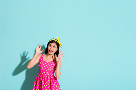 asian beautiful girl wearing a dotted pink cute dress standing on a blank blue background and showing surprising gestures and face happy expressions isolated on the blank copyspace area.