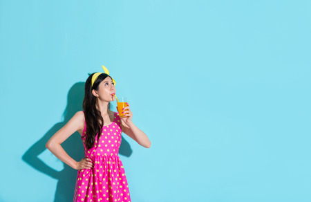 elegant attractive girl drinking orange juice looking at above of blue background daydreaming.