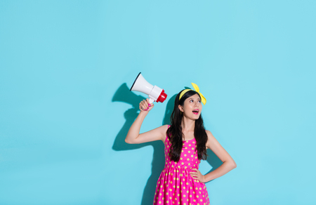 cheerful young lady wearing cute dress looking at empty area daydreaming and holding loudspeaker device standing in blue background. Stock Photo